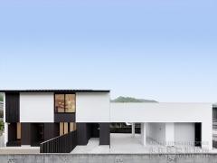 住宅部分と納屋を駐車場で繋いだ建物の昼景