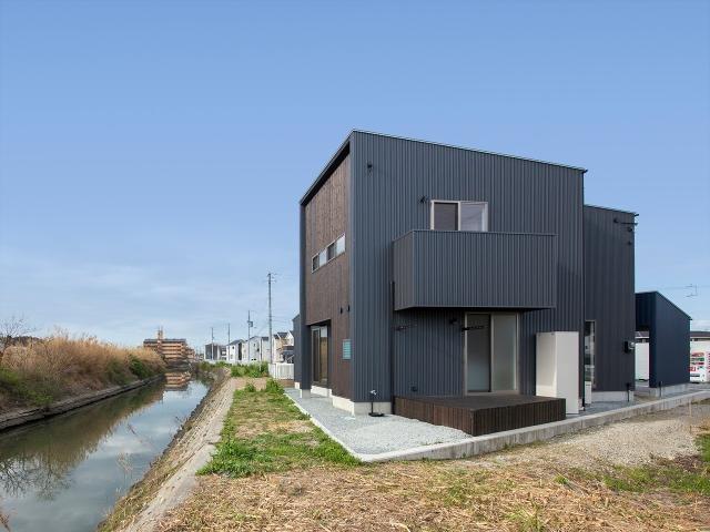 川沿いに建つ片流れ屋根の家 昼景