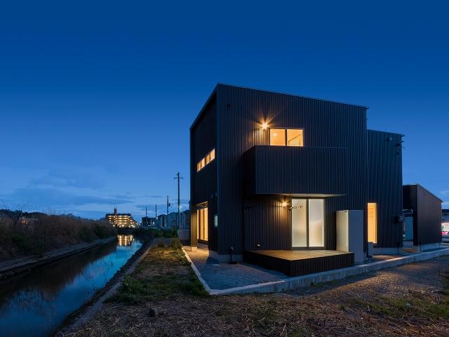 川沿いに建つ片流れ屋根の家 夕景