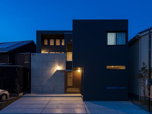 二階のベランダ高さまである、コンクリート打放しの壁がある家の外観!夕景