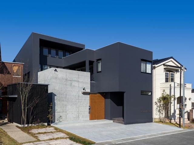 二階のベランダ高さまである、コンクリート打放しの壁がある家の外観!昼景