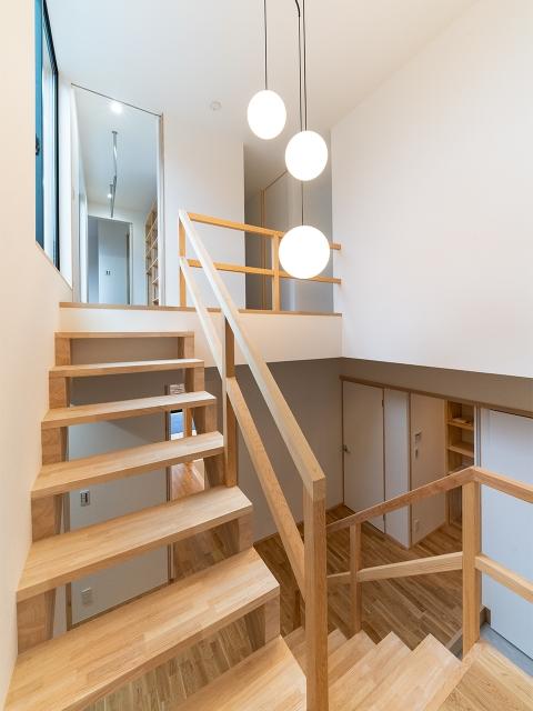 吹き抜けから光が差し込む玄関ホールの吹き抜けにあるオープンな階段2